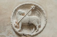 Lamb of God. With Holy Cross ancient white stone relief on a Venice wall Stock Photo