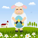 Lamb Holding a Easter Egg in a Meadow Royalty Free Stock Image