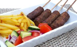 Lamb kebab with fries and salad Royalty Free Stock Images