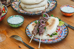 Lamb kebab on a traditional greek plate Royalty Free Stock Images