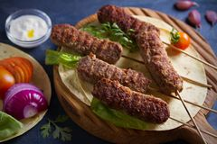 Lamb kebabs on serving board with pita bread, vegetables and yogurt sauce. Lamb kebabs on serving board with pita bread, vegetables and yogurt sauce stock image
