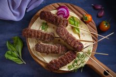 Lamb kebabs on serving board with pita bread, vegetables and yogurt sauce. View from above, top studio shot stock image