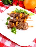 Lamb kebabs with yellow pepper and green salad on white plate Royalty Free Stock Images