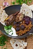 Lamb meal. Lamb loin with yellow peas and prunes in a frying pan, on a wooden board. The dressing is a seasoned yogurt from Middle East. Served with plain pita Royalty Free Stock Photos