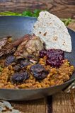 Lamb meal. Lamb loin with yellow peas and prunes in a frying pan, on a wooden board. The dressing is a seasoned yogurt from Middle East. Served with plain pita Royalty Free Stock Photo