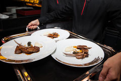 Lamb on plate already to served by waiter Royalty Free Stock Images