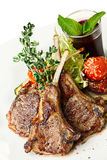 Lamb rack with garnish. Fried lamb rack with vegetable garnish. Lamb chop dinner Royalty Free Stock Photography