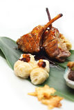 Lamb rack with unagi mashed potato. Served on banana leaf placed on white background Stock Images