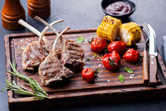 Lamb ribs grilled on cutting board with vegetables Stock Photos