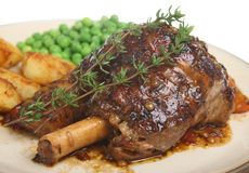 Lamb Shank. In a herb jus served with sauteed potatoes and peas Stock Photos