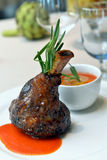 Lamb shank. With sauce on a white plate Stock Image