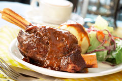 Lamb shank. Roasted lamb shank with whipped potato and salad Stock Photo