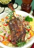 Lamb Shank. Roasted lamb shank on tomato, butternut pumpkin and parsley couscous Stock Photos