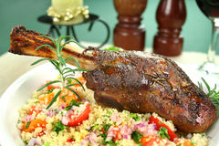 Lamb Shank On Cous Cous. Roasted lamb shank on tomato, butternut pumpkin and parsley cous cous Royalty Free Stock Image