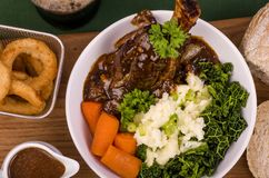 Lamb Shank Dinner. Traditional St Patrick's Day Lamb Shank served with mashed potato known as Colcannon Stout battered onion rings and a glass of Irish Stout Stock Photos