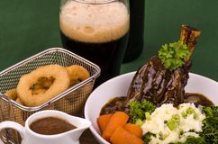 Lamb Shank Dinner. Traditional St Patrick's Day Lamb Shank served with mashed potato known as Colcannon Stout battered onion rings and a glass of Irish Stout Stock Photography