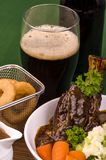 Lamb Shank Dinner. Traditional St Patrick's Day Lamb Shank served with mashed potato known as Colcannon Stout battered onion rings and a glass of Irish Stout Stock Image