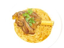 Lamb shank in juicy yellow rice Royalty Free Stock Images