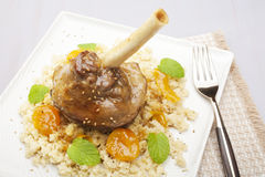 Lamb Shank Tagine. Moroccan tagine, lamb shank cooked with ginger, cinnamon, honey and apricots, served over couscous Stock Images