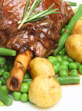 Lamb Shank with Vegetables. Roasted lamb shank with new potatoes, green beans and peas Royalty Free Stock Image