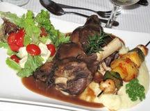 Lamb shanks. Main course of lamb shanks with roast veggie skewer and tomato and feta salad on potato mash and gravy Stock Photo