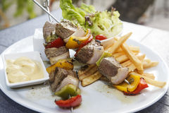 Lamb shish kebab on skewers. Lamb shish kebab on skewers with vegetables and fries on the side Royalty Free Stock Photo