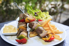Lamb shish kebab on skewers with vegetables. And fries on the side, with green blur background Stock Photos