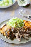 Lamb shoulder with dauphinoise potatoes, Savoy cabbage and roast carrots. On the dinner plate Royalty Free Stock Images
