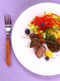 Lamb steak with gnocchi, red peppers and coriander Stock Photography