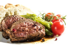 Lamb steak with green beans, tomatoes and bread  on a wh Royalty Free Stock Photography