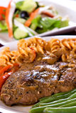 Lamb Steak with macarroni. Lamb steak closeup with crab meat salad in the background Stock Photos
