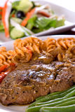 Lamb Steak with macarroni. Lamb steak closeup with crabmeat salad in the background Stock Image