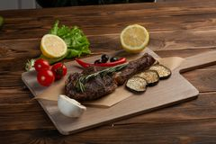 Lamb steak with vegetables and tomato sauce on a wooden background stock photography