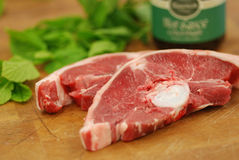 Lamb Steaks. On butcher's block with mint sauce and fresh mint Royalty Free Stock Photo