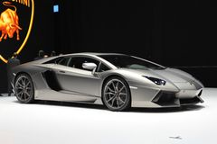 Lamborghini Aventador LP700-4. Silver Lamborghini Aventador LP700-4 on display in front of the Lamborghini logo Royalty Free Stock Photo