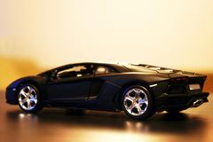 Lamborghini Aventador LP700-4 model car toy. Lamborghini Aventador LP700-4 die-cast metal model toy 1:24 scale, Black. Lateral view Royalty Free Stock Photo