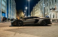 Lamborghini Aventador luxury sport carbon car parked on Kensignton Street in London. LONDON, UNITED KINGDOM - MAR 9 2017: Rich businessmen party on the balcony stock photos