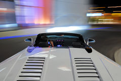 Lamborghini Spyder Driving. A white Lamborghini Gallardo Spyder Supercar speeding down the street Royalty Free Stock Photos