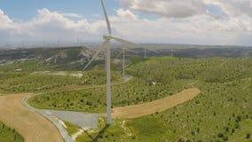Lame del generatore eolico che girano sulle colline verdi stupefacenti, fonte di energia alternativa archivi video