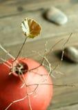 Lame verte sur les brindilles sèches dans un vase et des pierres à argile Photographie stock