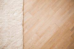 Lamellenförmig angeordneter parquete Boden mit beige weichem Teppich lizenzfreies stockbild