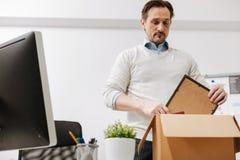 Lamentabeles Belegschaftsmitglied, das den Kasten verpackt und das Büro verlässt Stockfotos