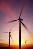 Lames de turbine de turbines de vent tournant au coucher du soleil Photographie stock libre de droits