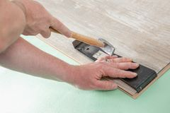 Laminate fitting. A Carpenter is fitting two pieces of Laminate with a hammer and a laminate tool stock photography