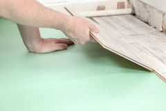 Laminate fitting. A man is trying to fit a piece of laminate to an other one stock photo