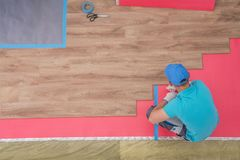 Laminate Flooring Installing. By Professional Caucasian Installer. Remodeling Worker From Above royalty free stock images
