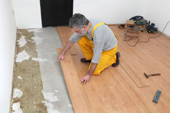 Laminate flooring of room. Adult male worker installing laminate floor, floating wood tile stock images