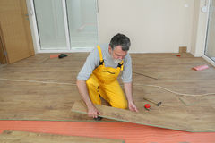 Laminate flooring of room. Adult male worker installing laminate floor,  floating wood tile Royalty Free Stock Photography