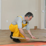 Laminate flooring of room. Adult male worker installing laminate floor, floating wood tile stock photos