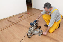 Laminate flooring of room, batten cuting. Worker cut wooden batten for laminate floor, floating wood tile stock image